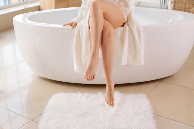 Красивая молодая женщина после депиляции ног в ванной комнате