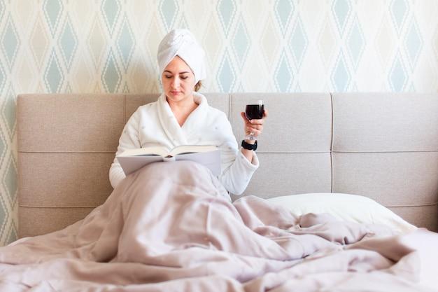 Красивая молодая женщина после душа в халате и с полотенцем на ее волосы. девушка лежит на кровати с бокалом красного вина в домашних условиях и читает книгу