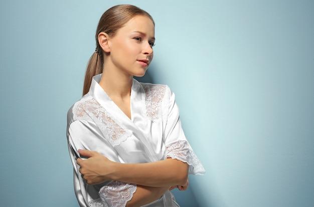 Красивая молодая женщина после душа в шелковом халате на светлой поверхности