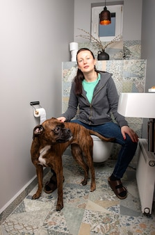 自宅のトイレのインテリアで美しい若い女性とボクサー犬
