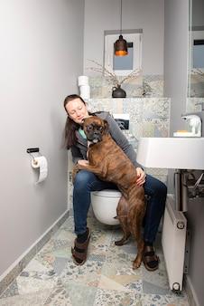家庭用トイレのインテリアで美しい若い女性とボクサー犬