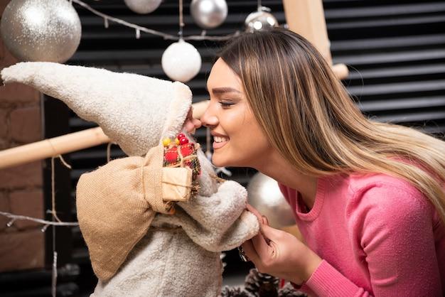 美しい若い女性と人形がお互いを見つめています。