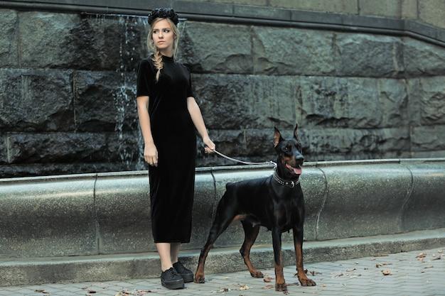 아름 다운 젊은 여자와 그녀의 강아지 분수 근처