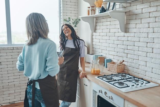 Красивая молодая женщина и ее мать общаются, проводя время на домашней кухне