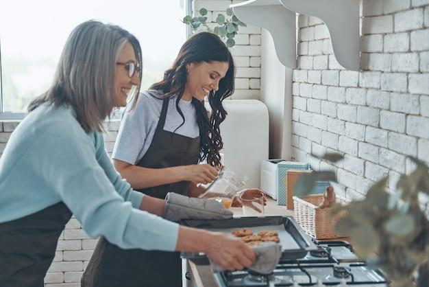 Красивая молодая женщина и ее мать готовят вместе, проводя время на домашней кухне