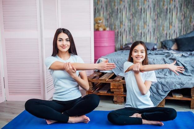 美しい若い女性と彼女の陽気な娘はマットの上で運動をしています