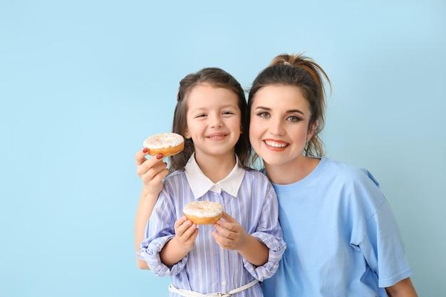 Красивая молодая женщина и маленькая девочка с пончиками