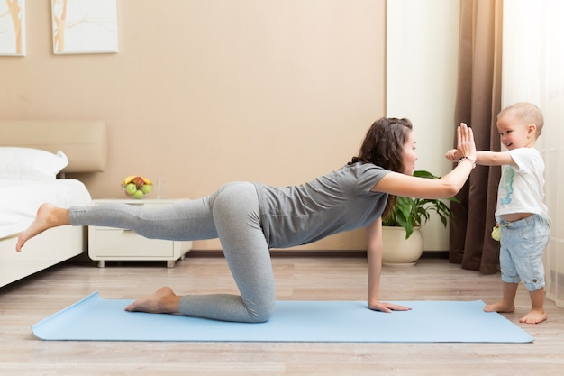 Красивая молодая женщина и маленький мальчик улыбается, лежа на коврике для йоги и делая фитнес-упражнения дома