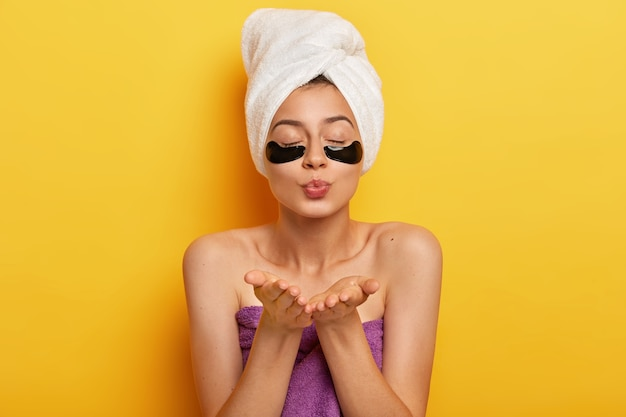 Красивая молодая женщина накладывает коллагеновые пластыри для удаления морщин, посылает воздушный поцелуй, держит глаза закрытыми, носит белое полотенце на голове