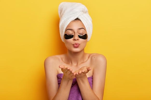 Bella giovane donna applica cerotti di collagene per rimuovere le rughe, manda un bacio d'aria, tiene gli occhi chiusi, indossa un asciugamano bianco sulla testa