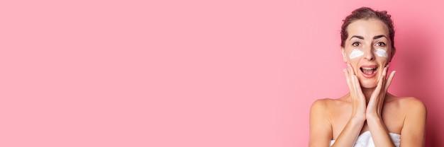美しい若い女性はピンクの背景に彼女の顔にクリームを適用します