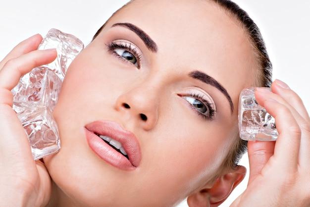La bella giovane donna applica il ghiaccio al fronte. concetto di cura della pelle.