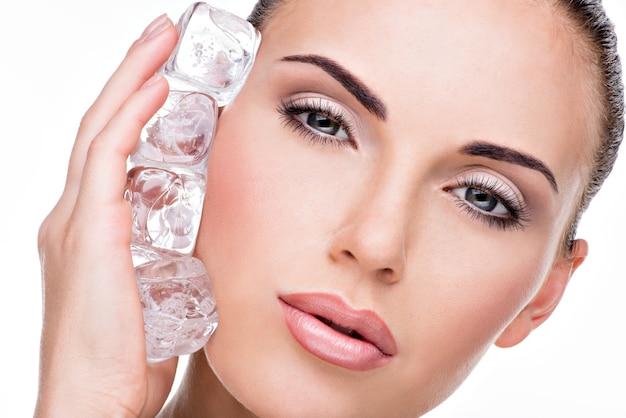 La bella giovane donna applica il ghiaccio al fronte.