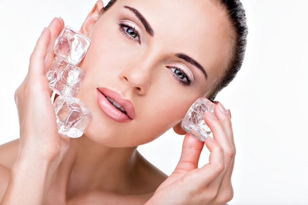 Beautiful young woman applies the ice to face.