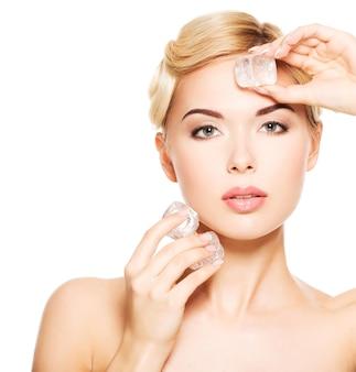 아름 다운 젊은 여자는 얼굴에 얼음을 적용합니다. 스킨 케어 개념. 흰색으로 격리.