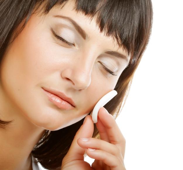 Красивая молодая женщина, применяя крем на лице, изолированном на белом фоне