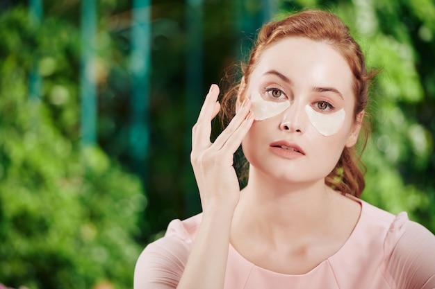 다크 서클을 없애기 위해 눈 밑 패치를 밝게 하고 보습을 적용하는 아름다운 젊은 여성