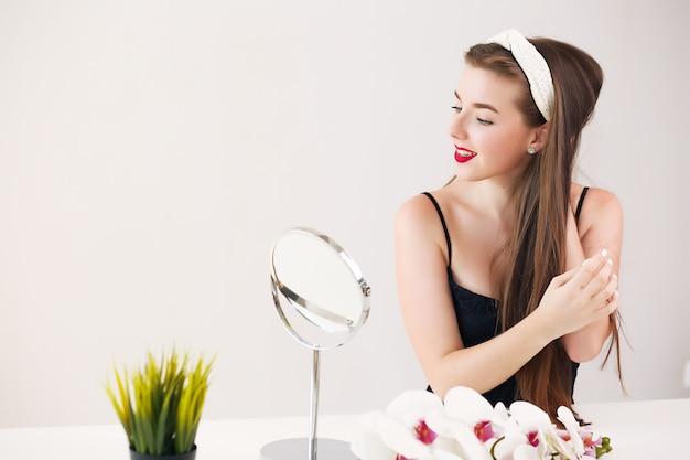 自宅で彼女の髪にココナッツオイルを適用する美しい若い女性