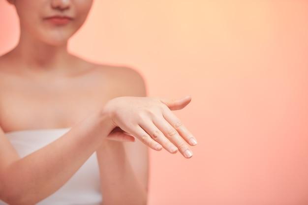 Красивая молодая женщина, наносящая косметический увлажняющий крем на руки