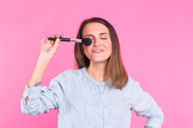 タッセル、スキンケアのコンセプトで彼女の顔に化粧品の粉を適用する美しい若い女性。