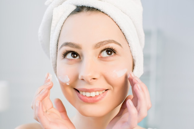 Beautiful young woman applying cream on her face in bathroom. treatment for perfect skin concept