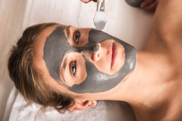 Beautiful young woman applying face mask on her face