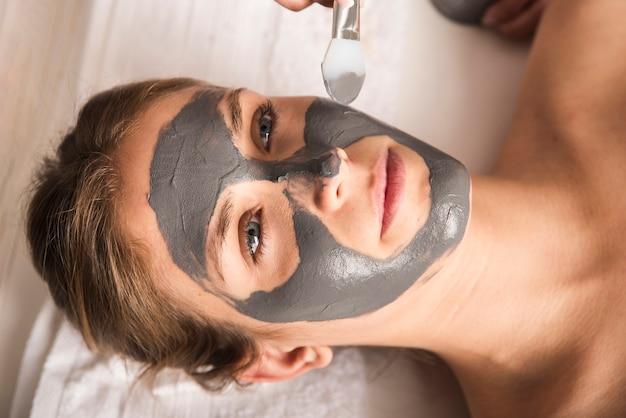 그녀의 얼굴에 얼굴 마스크를 적용하는 아름 다운 젊은 여자