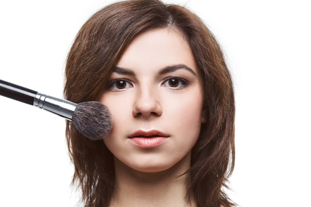 タッセル、ブルネットの少女のスキンケアコンセプト写真の構成で彼女の顔にファンデーションを適用する美しい若い女性-白い背景で隔離