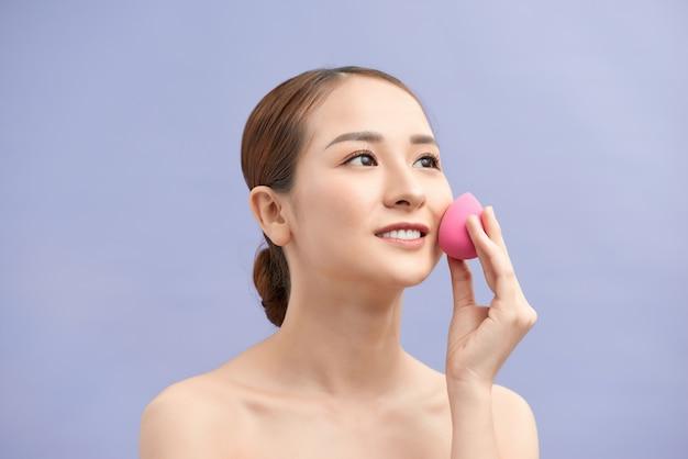 뷰티 블렌더 스폰지를 사용하여 메이크업을 적용하는 아름 다운 젊은 여자.