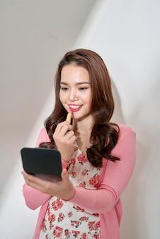 小さな鏡を見ながら、ピンクの口紅を塗る美しい若い女性。