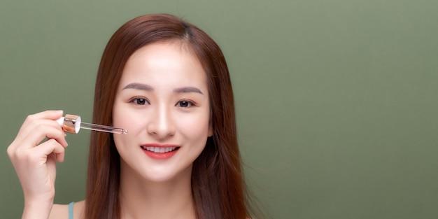 Красивая молодая женщина наносит сыворотку на кожу на цветном фоне