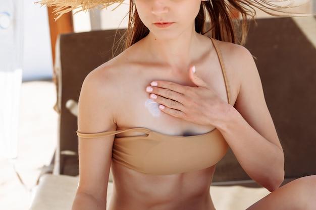 복사 공간 바다에서 선탠 로션을 적용하는 아름 다운 젊은 여자. 열 대 해변에서 어깨에 자외선 차단제를 적용하는 비키니 입은 무두 질된 소녀. 자외선 차단 크림으로 피부를 보호하는 여성.