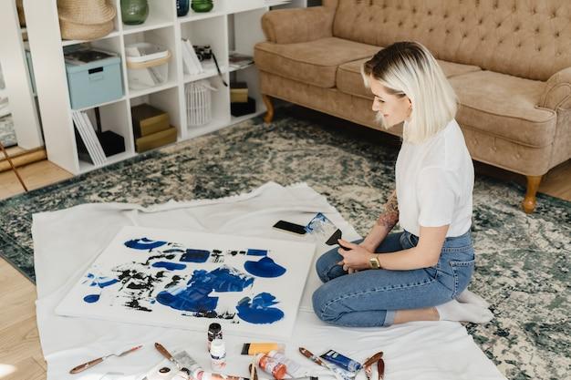 Художник красивая молодая женщина рисует в удобном домашнем интерьере