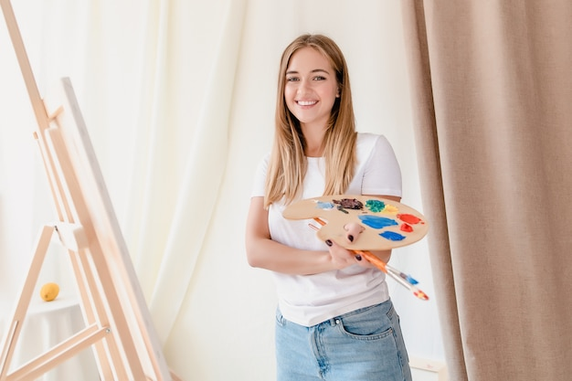 Beautiful young woman artist drawing a picture on canvas at home