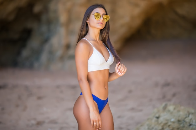 カメラ目線のビーチで美しい若い女性。白いビキニを笑顔で幸せなラテンの女の子。