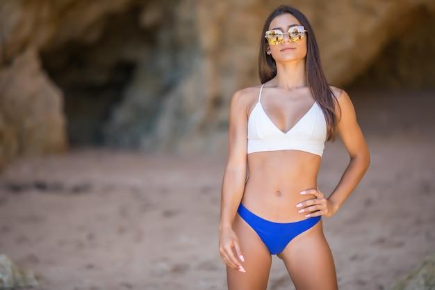 카메라를보고 해변에서 아름 다운 젊은 여자. 흰색 비키니 미소에 행복 라틴 여자입니다.
