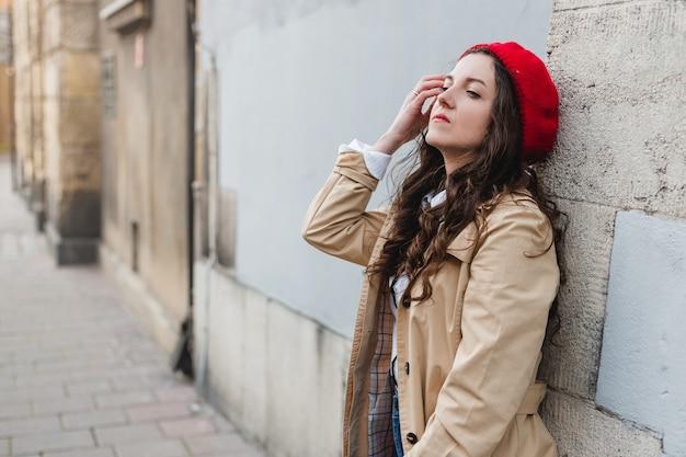 街の通りで美しい若い女性。屋外を歩く幸せな観光客の女の子。旧市街でポーズをとるかわいいブルネットの女性の春のファッションの肖像画。