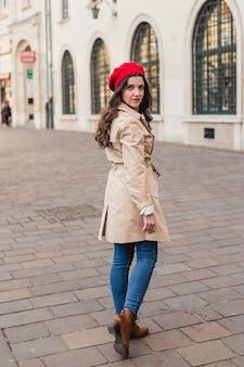 街の通りで美しい若い女性。屋外を歩く幸せな観光客の女の子。旧市街でポーズをとるかわいいブルネットの女性の春の全身ファッションの肖像画。