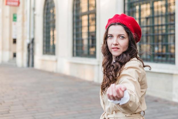 街の通りで美しい若い女性。屋外を歩く幸せな観光客の女の子。旧市街でポーズをとってかなりブルネットの女性の春の肖像画。街に私に従ってください