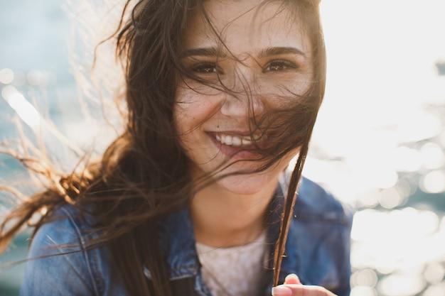 Красивая молодая женщина в океане, стоя на фоне бирюзового синего моря с волосами, развевающимися на ветру