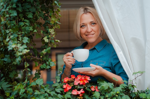 Beautiful young woman on the balcony with flowers, and white curtain enjoying a morning cup of coffee.