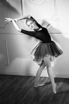 Красивая молодая женщина-балерина танцует с балетной пачкой
