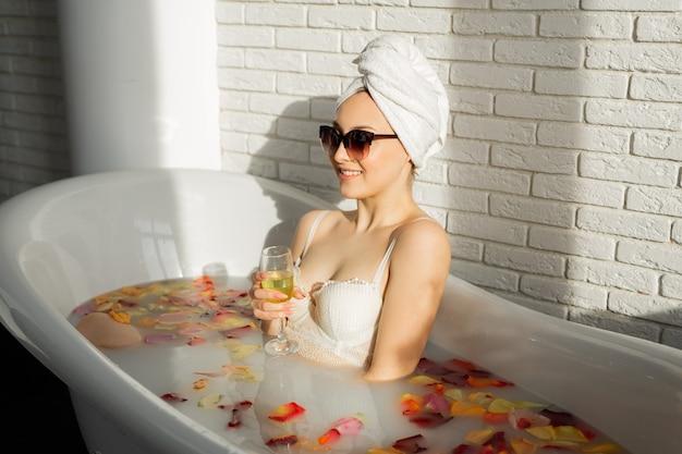 Красивая молодая женщина купается в ванне с лепестками роз с бокалом шампанского в солнечных очках