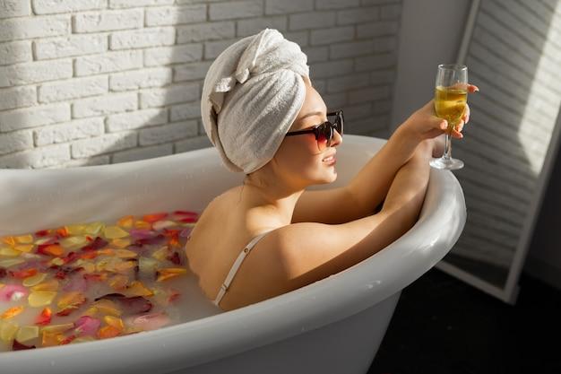 Красивая молодая женщина купается в ванне с лепестками роз с бокалом шампанского