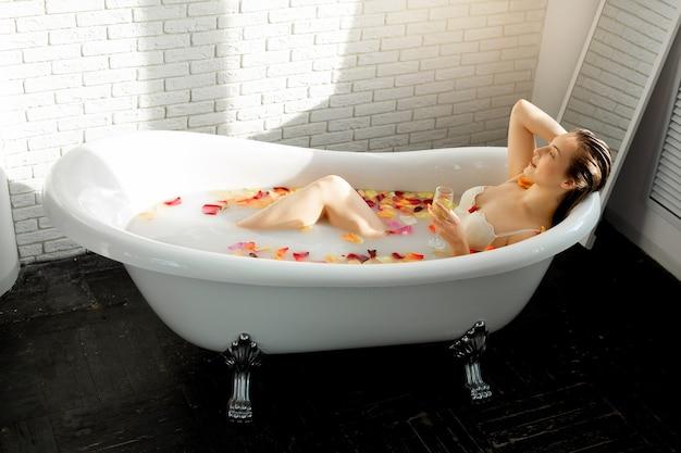 Красивая молодая женщина купается в ванне с лепестками роз