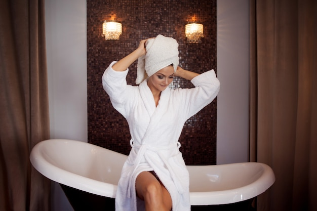 Beautiful young woman in bathrobe and towel on head. girl after bath