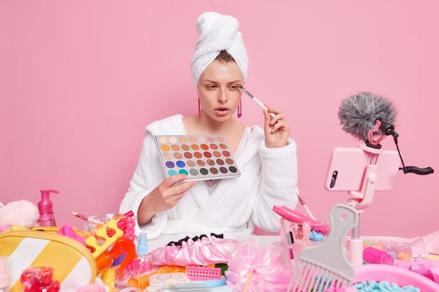 Beautiful young woman in bathrobe towel on head reviews cosmetic shows how to do makeup