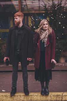 Beautiful young woman and bearded man holding coffee while standing in street