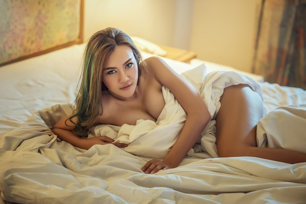Beautiful young woman in bedroom at home
