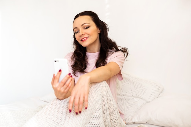 Beautiful young woman in the bedroom sitting on the bed with a mobile phone
